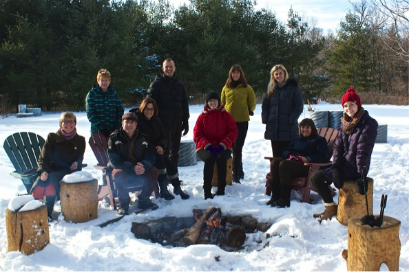 Photo of hhe team members taken around campfire at December 2014 team retreat