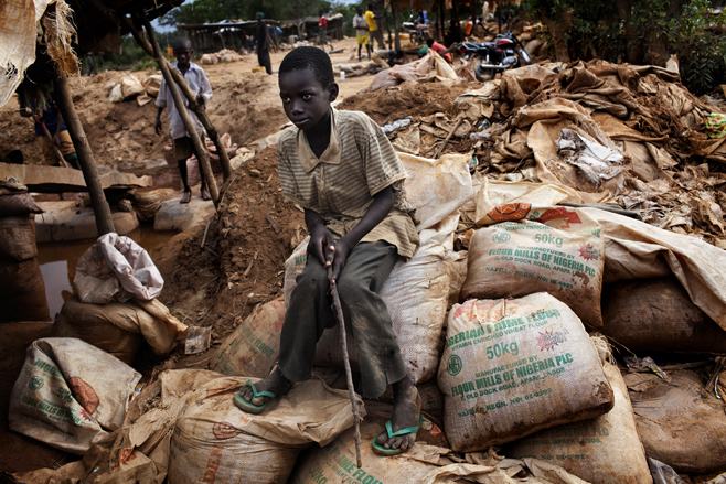 A young boy sits on a stack of ore sacks in the mining processing site in Bagega village. © 2011 Marcus Bleasdale/VII for Human Rights Watch http://www.hrw.org/news/2012/12/06/nigeria-death-stalking-lead-poisoned-children Photo credit for top photo: http://www.evidence4action.net/e4a-weekly-news-roundup-week-4/
